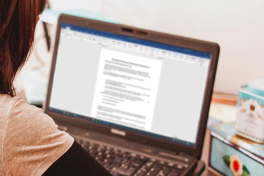 Pantalla del portátil con un documento de Word abierto; escorzo trasero de parte de la cabeza y el brazo de M.ª Carmen.